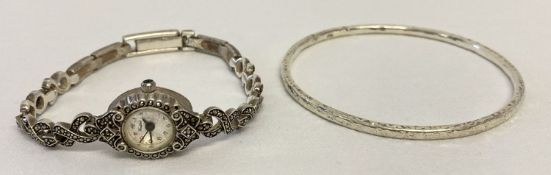 A silver bangle with hammered effect decoration marked 925.