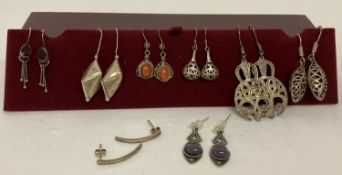 8 pairs of silver and white metal drop style earrings.