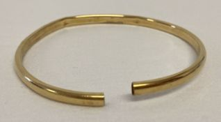 A cut through scrap gold bangle with indistinct marks to outside rim.