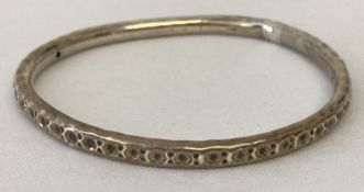 A silver bangle with punched star decoration. Very worn hallmarks, bangle has been altered.