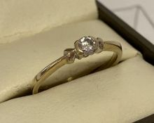 A 9ct gold .15ct diamond solitaire ring with heart detail to each side of stone.
