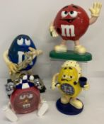 2 large M&M's advertising sweet dispensers, one playing a saxophone.