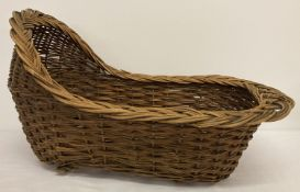 A vintage hand woven willow dolls rocking cradle.