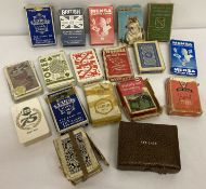 A collection of vintage playing cards, mostly boxed.