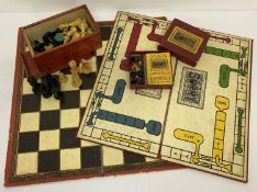 A box of vintage carved wooden chess board pieces with a Chad Valley folding chess board.