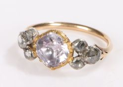 Gold coloured metal ring, the central purple paste flanked by three rose cut diamonds to each