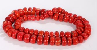 Substantial coral necklace, formed from graduated coral discs, the largest 34.5mm diameter, 104cm