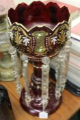 Victorian lustre, the ruby glass body with white and gilt foliate decoration and clear glass hanging
