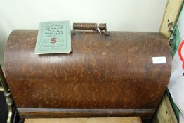 Singer sewing machine housed in a domed oak case