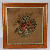 19th Century embroidery, with a central bouquet of flowers housed within a maple frame, 55cm x
