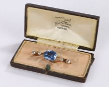 Sapphire and diamond set brooch, the oval light blue sapphire at 5.76 carats flanked by two round