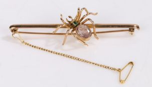9 carat gold insect brooch, as a spider with a pink gemstone and emerald to the back, 75mm long, 8.5