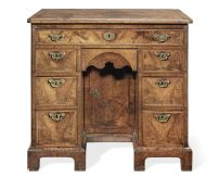 A George I walnut crossbanded and feather banded kneehole desk