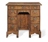 A George II walnut, crossbanded and feather banded kneehole desk