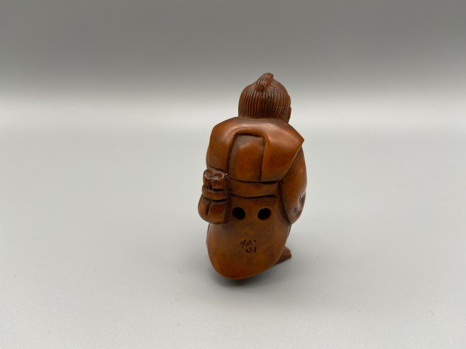 Lot 43J - Japanese hand carved netsuke of a gentleman holding a koi carp with black bead eyes, signed by the