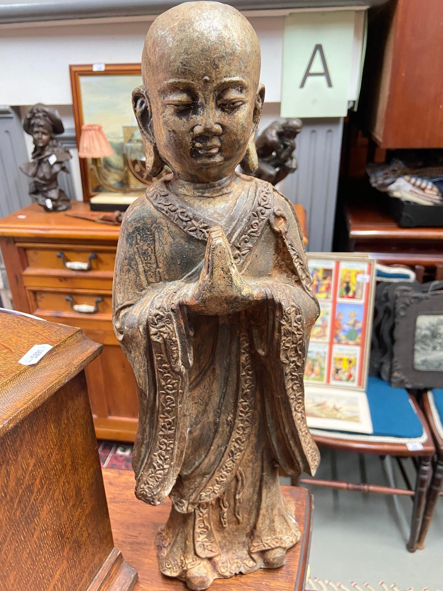 Lot 19 - A 19th century Chinese cast iron Monk figure.Showing signs of original gold colouring coming