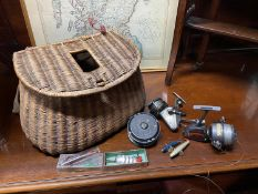 Antique fishing creel containing various fishing reels and lures