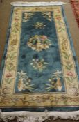 Chinese Rug, Decorated with allover floral medallions on a blue ground, 185cm x 90cm