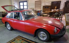 1977 MGB GT 1.8L. Red with black vinyl, showing 20,400 miles unchecked. Offered for restoration.