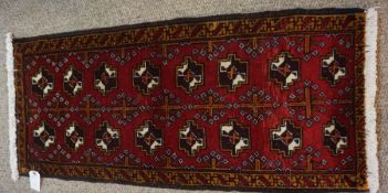 Turkoman Prayer Mat, Decorated with eight rows of two geometric motifs on a red ground, 98cm x 43cm