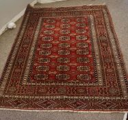 Turkoman Rug, Decorated with nine rows of three geometric motifs on a red ground, 156cm x 125cm