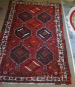 Persian Shiraz Rug, Decorated with three rows of two Geometric Medallions on a Red ground, 270cm x