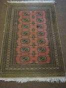Pakistani Rug, Decorated with seven rows of two Geometric Medallions on a Pink ground, 150cm x 99cm