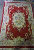 Chinese Style Rug, Decorated with Floral Motifs and Medallions on a Red ground, 195cm x 125cm