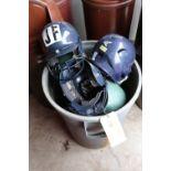 Trash can full of batting helmets