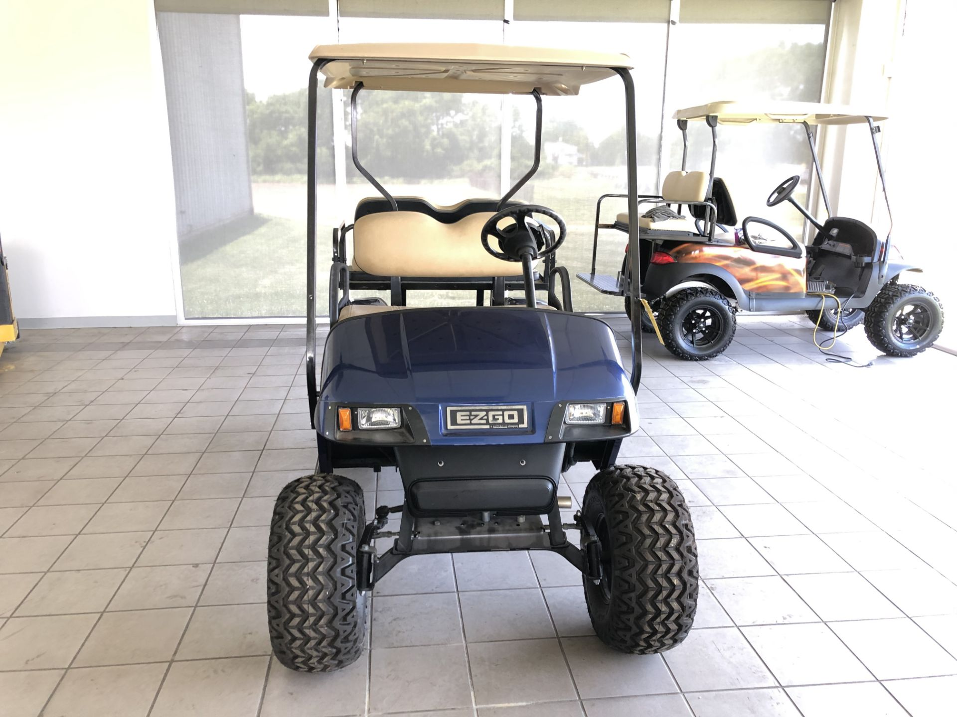 Lot 27 - 2012 EZ GO GOLF CART, GASOLINE, 4-PASSENGER FOLD DOWN SEAT, LIFT KIT, HEADLIGHTS/BRAKE-LIGHTS, NEW