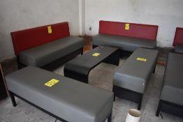 Sala tipo lounge que incluye dos sillones de tres plazas, dos taburetes y mesa de centro