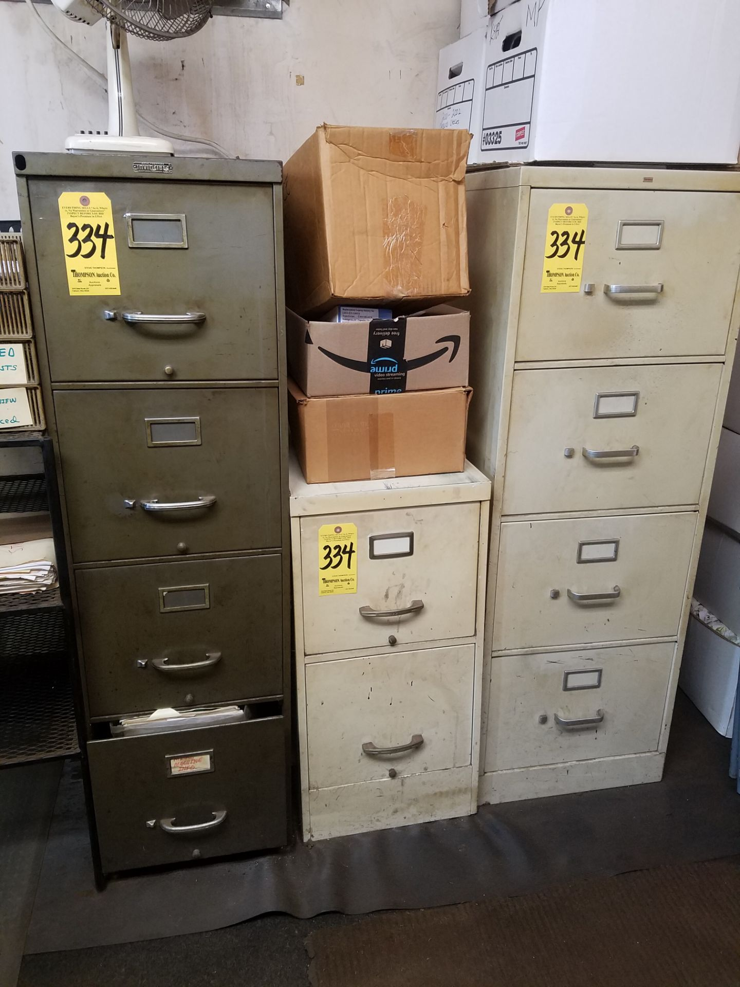 Lot 334 - (3) 4-drawer and (1) 2-drawer file cabinets, fax machine, metal desk, and wood credenza.