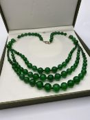 A graduating green jade necklace in a presentation box.