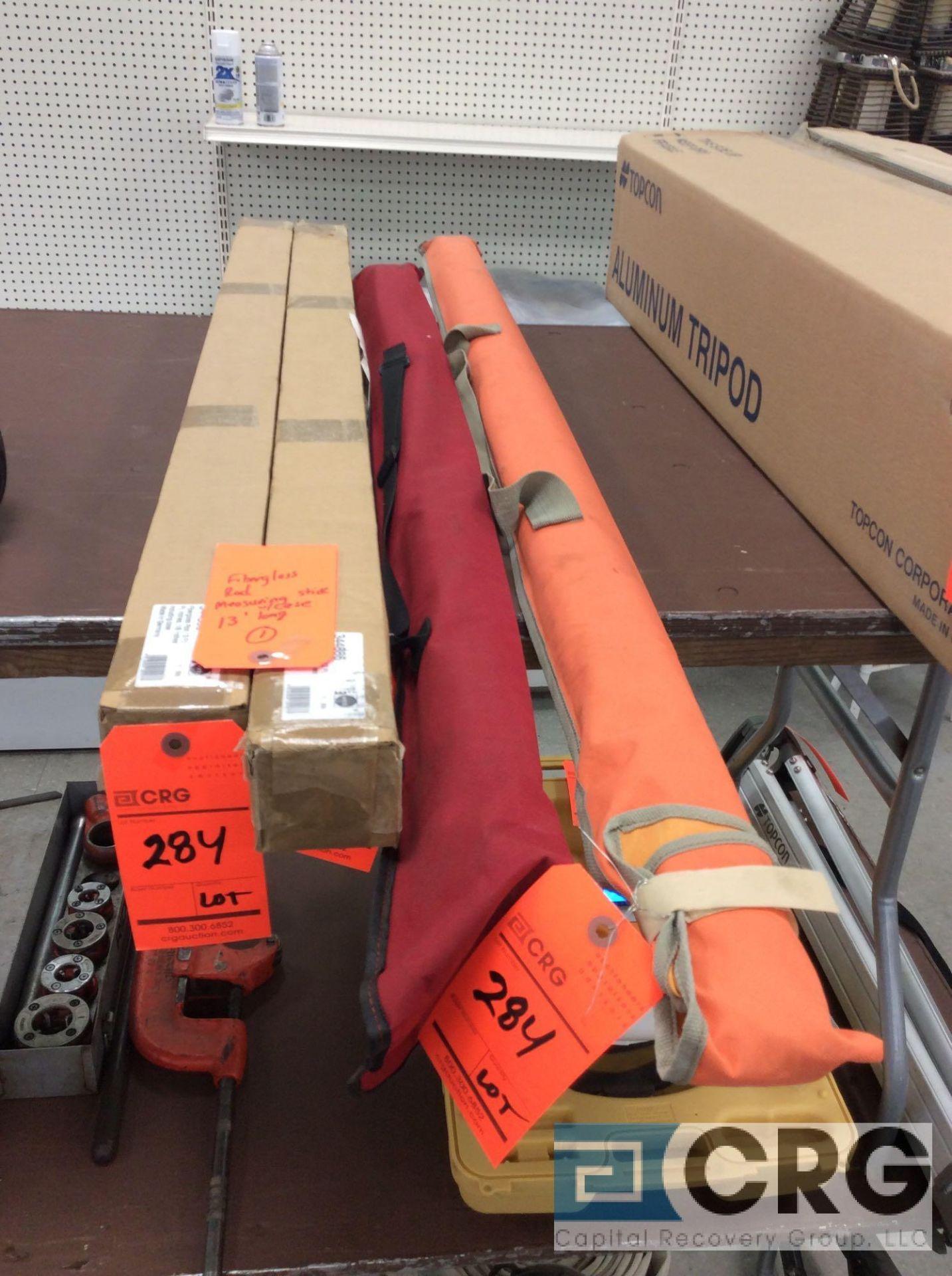 Lot of (4) fiberglass measuring sticks with bag case