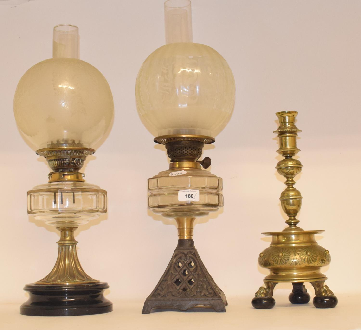 Lot 180 - A late 19th/early 20th century brass oil lamp, with engraved glass shade, four other oil lamps and a
