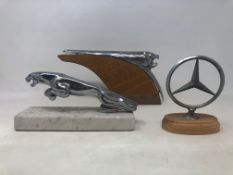 A chrome leaping Jaguar bonnet mascot, lacks tail, on a marble base, and two other hood ornaments