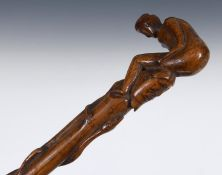 A 19th century folk art walking stick, the handle carved in the form of a naked woman crouched