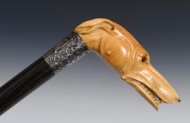 A 19th century walking stick, with a carved ivory handle in the form of a greyhound bearing its