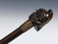 An early 20th century walking stick, with a carved wooden handle in the form of a military figure in