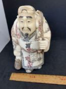 Chinese or Japanese looking figure of a man carrying fish signed on the bottom