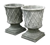 A pair of reconstituted stone urns of classical form, each 46cms (18ins) diameter (2).