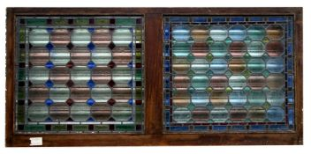 Two stained glass panels in an oak frame, 174 by 86cms (68.5 by 34.5ins) two similar framed