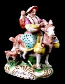 A Staffordshire pottery group, in the form of a woman with children riding a goat