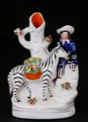 A 19th century Staffordshire spill vase depicting a figure with a zebra, 16cms (6.25ins) high.