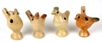A group of four pottery whistles, three in the form of birds and one in the form of a pig, the