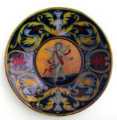 A maiolica dish decorated with a central winged cherub, 23cms (9ins) diameter (a/f).Condition