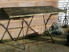 A French wood and wrought iron garden table, 125cms (49ins) wide; together with four matching chairs