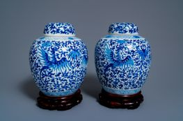 A pair of Chinese blue and white 'phoenix' jars and covers with floral design, Kangxi mark, 19th C.