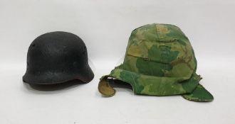 World War II German helmet together with one further helmet in camouflagecover