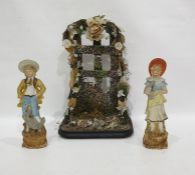 Pair late 19th century tinted bisque figures of boy and girl with birds and a floral applied